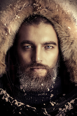 Portrait of a handsome brutal man with beard and mustache dressed in winter clothes, covered with frost. Фото со стока