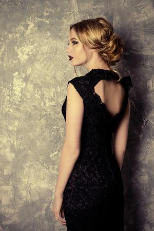 Vogue shot of a beautiful young woman with dark make-up. Cosmetics, maroon lipstick. Studio shot.