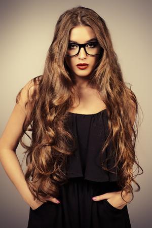 Optics style. Beautiful sexy girl with long wavy hair wearing glasses. Fashion studio shot. Cosmetics, make-up. Red lipstick.