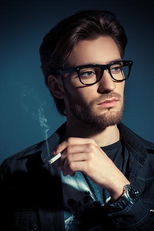 Attraente giovane uomo pensieroso e con calma fumare una sigaretta. la bellezza maschile, moda. stile Optics.