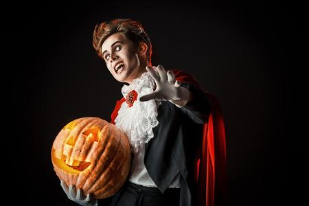 Portrait of a handsome vampire with pumpkin. Halloween. Dracula costume.