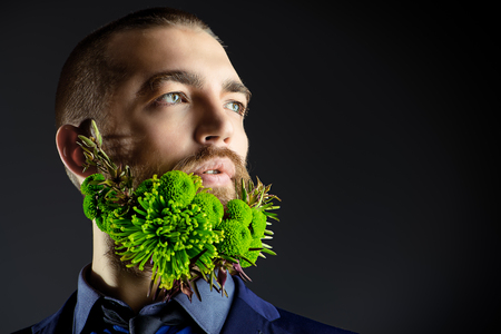 Portrait of a handsome man with a beard of green flowers. Mens beauty. Barbershop. Copy space. Stock Photo