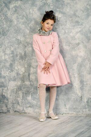 Elegant eight-year girl in pink coat. Kid's fashion.