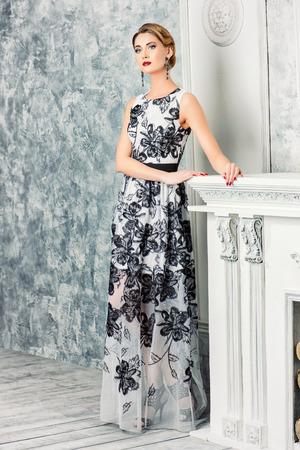 Retrato de cuerpo entero de una mujer encantadora en vestido de noche hermosa de pie junto a una chimenea en una habitación con un interior clásico de la vendimia. Joyería. Captura de moda. Peinado. Foto de archivo