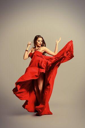Mujer sexual hermosa en vestido de noche rojo que presenta en movimiento. Moda tiros en el estudio.