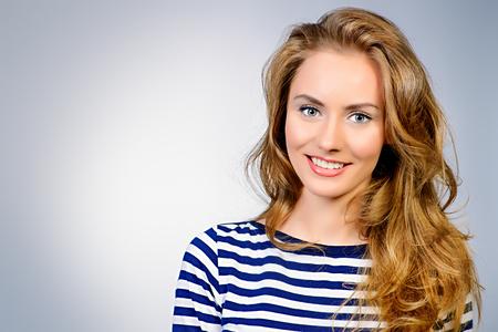 Pretty woman with beautiful long hair smiling at camera. Studio shot.