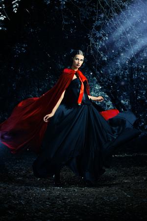 Hermosa mujer morena en vestido anticuado negro y capa roja caminar en la espesura del bosque mágico. Estilo gótico. Moda.