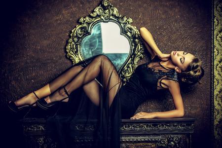 Giovane donna elegante in abito da sera nero in posa in interni d'epoca. Adatti il ??colpo.
