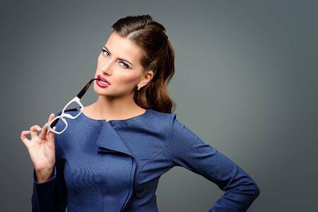Optics style. Portrait of a beautiful young woman wearing elegant glasses. Beauty, fashion. Cosmetics, make-up. 免版税图像