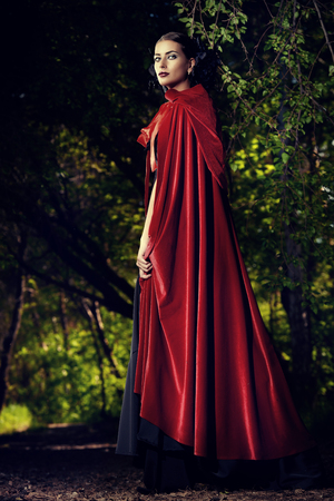 Beautiful brunette woman in black old-fashioned dress and red cloak walking in the thicket of the magic forest. Gothic style. Fashion. Banco de Imagens