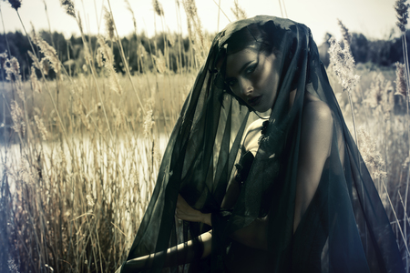 Beautiful brunette woman wearing long black dress and black veil posing among the reeds. The old times, the Gothic style. Fashion.