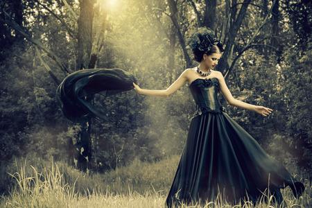 신비한 숲에서 긴 검은 드레스 산책을 입고 웅대 한 갈색 머리 여자. 옛날, 고딕 스타일. 유행.
