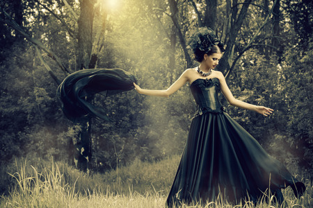 Magnificent brunette woman wearing long black dress walking in a mystic forest. The old times, the Gothic style. Fashion. Stock fotó - 58604765
