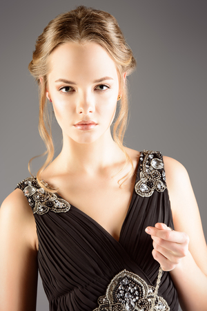 Jolie jeune femme en petite robe noire. Beauté, mode. Studio shot.