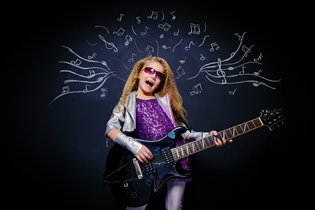 Little rock star singing with her electric guitar over musical background. Music concept. Banque d'images