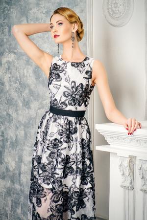 Ritratto di una donna affascinante nel bellissimo abito da sera in piedi da un caminetto in una stanza con l'Inter classica annata. Gioielleria. Moda girato. Acconciatura. Make-up, cosmetici.