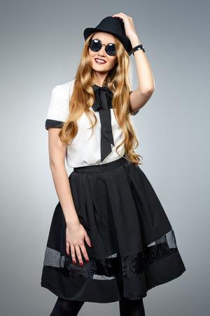 Modella posa. Bella giovane donna che indossa bella camicetta e la gonna. Ritratto in studio su sfondo grigio.