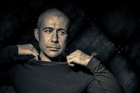 Close-up portret van een man in zwarte kleding over donkere grunge achtergrond. Stockfoto - 59135334