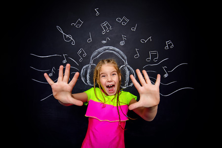 Cheerful little girl enjoys the music in headphones. Studio shot. Reklamní fotografie - 59182235