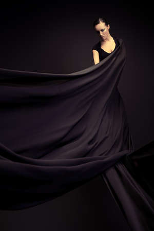 Art fashion photo of a beautiful woman in black dress. Over black background. Imagens