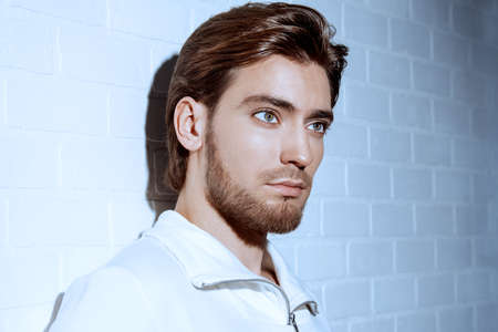 Ritratto di bellezza di un bel pensieroso giovane uomo in piedi da un muro di mattoni bianchi. Archivio Fotografico