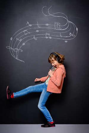 표현 십 대 소녀 마이크와 노래를 노래를 즐깁니다. 세대. 스튜디오 촬영.