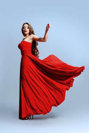 Hermosa mujer sexual en vestido de noche rojo posando en movimiento.