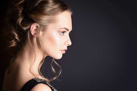 Portrait in profile of a beautiful girl with an evening make-up and hairstyle.