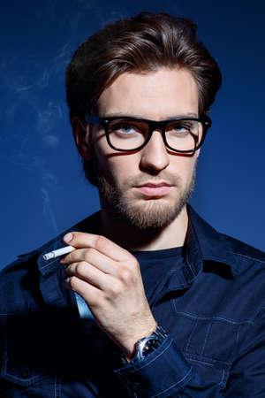 Giovane attraente pensieroso e tranquillamente fumando una sigaretta.