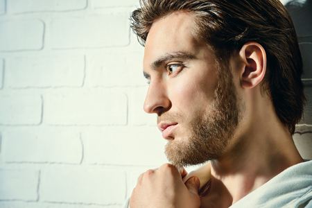 Beauty portrait of a handsome pensive young man standing by a white brick wall.