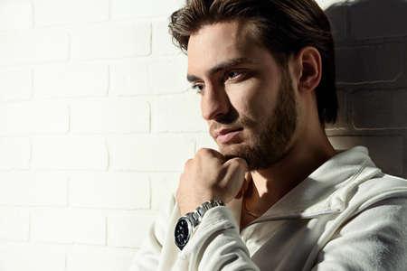 Ritratto di bellezza di un bel pensieroso giovane uomo in piedi da un muro di mattoni bianchi.