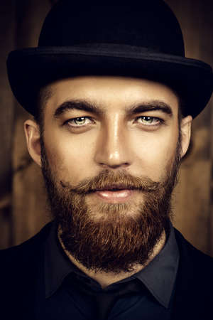 Elegant man with beard and mustache wearing suit and bowler hat. Old style fashion. Фото со стока