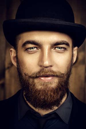hombre elegante, con barba y bigote, vistiendo traje y bombín. la moda de estilo antiguo. Foto de archivo