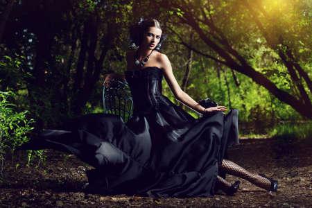 Bella donna gotica che indossa lungo vestito nero che propone in una foresta mistica.