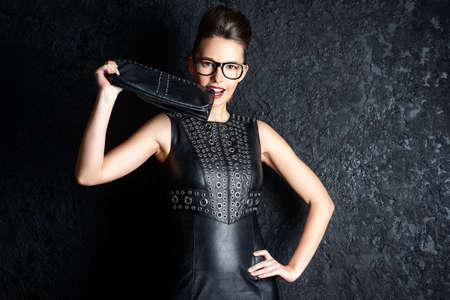 Atractiva atractiva mujer joven en traje de cuero negro sobre fondo negro. Belleza, moda. El estilo de negocios. Foto de archivo