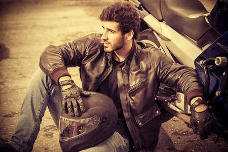 Sexy biker man noszenie dżinsy i skórzana kurtka zrelaksowany przez jego motocykl. Zdjęcie Seryjne