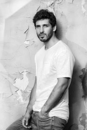 Black-and-white portrait of a handsome young man in jeans and white t-shirt leaning to the old wall.