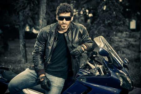 ジーンズと座っている革のジャケットを身に着けているセクシーなバイカー男は、自分のバイクでリラックス。