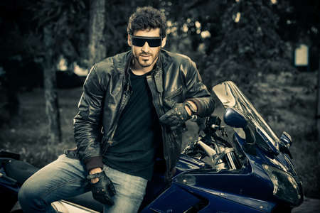 Sexy biker man wearing jeans and leather jacket sitting relaxed on his motorcycle.