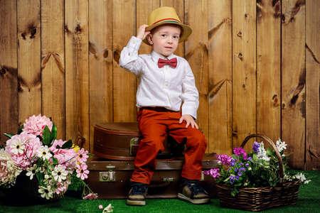 Schattige kleine jongen in een elegante kleren zitten op zijn oude koffers op een groen gazon met bloemen op houten achtergrond. Kid's mode. Kindertijd. Zomervakantie.