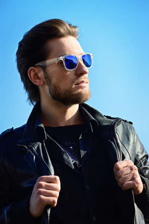 Confident handsome man in sunglasses and leather jacket over blue sky. Mens beauty, fashion. Outdoor portrait. Reklamní fotografie