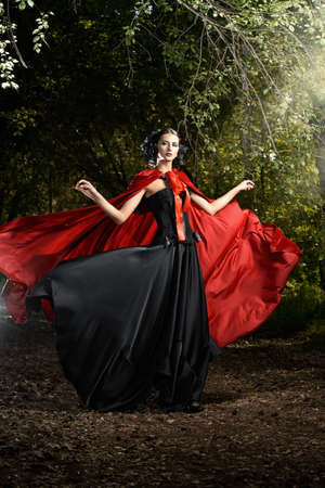 Beautiful brunette woman in black old-fashioned dress and red cloak walking in the thicket of the magic forest. Gothic style. Fashion. Stok Fotoğraf