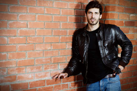 Portrait of a handsome brunet man in black leather jacket standing by a brick wall. Stock Photo