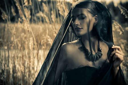 아름 다운 갈색 머리 여자 긴 검은 드레스와 검은 베일 갈 대 중 포즈를 입고. 예전에는 고딕 양식이었습니다. 유행. 스톡 콘텐츠