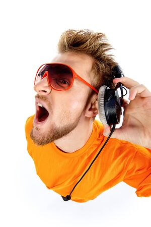 Happy young stylish man in headphones enjoying the music and expressing positivity. Isolated over white.