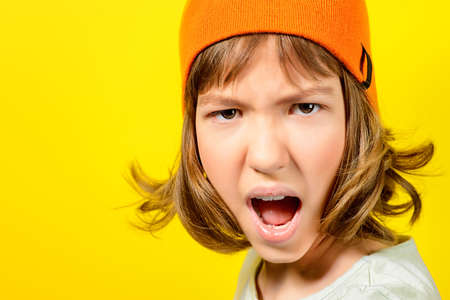 Portrait of a shouting angry teen girl over yellow background. Modern generation. Copy space. Stock Photo