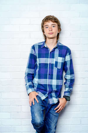 Portrait of a teenage boy standing by a white brick wall. Studio shot. Teen fashion.