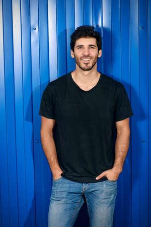 青い金属フェンスによって街の通りの上に立って魅力的な男性的な男性。男性美容、ファッション。 写真素材