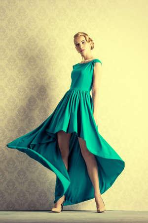 Moda ritratto di una giovane e bella donna in abito da sera elegante che propone in movimento da un muro d'epoca. Acconciatura.