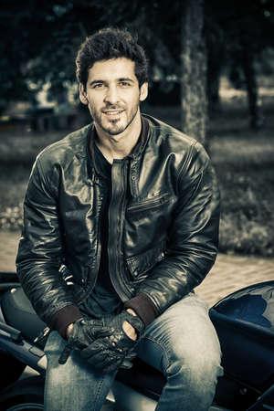 Hombre atractivo del motorista con pantalones vaqueros y chaqueta de cuero sentado relajado en su motocicleta. Foto de archivo